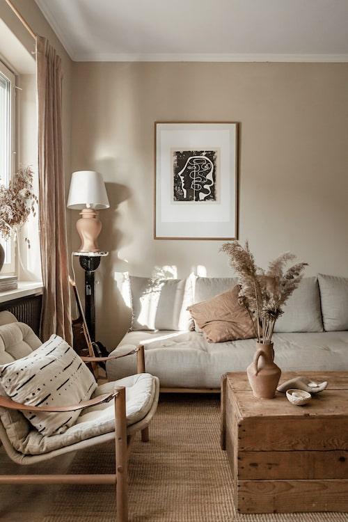 Mild färgharmoni råder i vardagsrummet. Soffan är från danska Karup design. Brunrosa kudde, Poudre organic, poster av Ben Nicholson, Tate shop, fåtölj, vintage Bror Boije, svart piedestal och keramiklampa är båda vintagefynd.