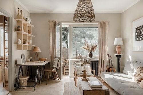 Solen lyser in i det trivsamma vardagsrummet som rymmer såväl soffa som arbets- och matplats. Taklampa från AB Småland, skrivbordslampan är vintage och vägghylla och stol, Ikea.