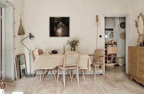 Vägglampan och matbordet är båda hemmabyggen, stolarna kommer från Ellos. Det svartvita fotot är en gåva från fotografen Hannah Lemholt. Golvlampa, Ikea, vasen och kvasten av palmlöv är från Tine K, tekanna, vintage.