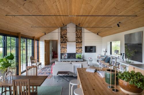 """Den öppna spisens vedstaplar går ända upp till tak. Soffan har placerats som en rumsavdelare mellan vardagsrum, matplats och kök. Tunna """"takstolar"""" av metall lättar upp intrycket och behåller rymden. Till höger, platsbyggda hyllor och förvaring med inbyggd bänk som binds ihop med köksinredningen."""