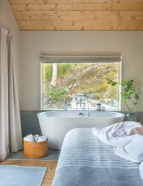 Öppen planlösning är ett koncept som kan appliceras på fler ställen än mellan kök och vardagsrum! Badkarets placering är valt med omsorg och har en härlig utsikt. Här behövs inga tavlor på väggarna, här står naturen för utsmyckningen.