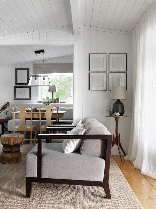 """Det lackade furugolvet i vardagsrummet har Geir låtit vara i sitt originalskick. """"Jag brukar säga att ingen tänker på golvet ändå när de ser hur jag inrett"""" - säger Geir och skrattar gott. En matta från Ikea gör känslan varm och ombonad. Fåtöljer med svarta karmar och soffbord köpta på Blocket."""