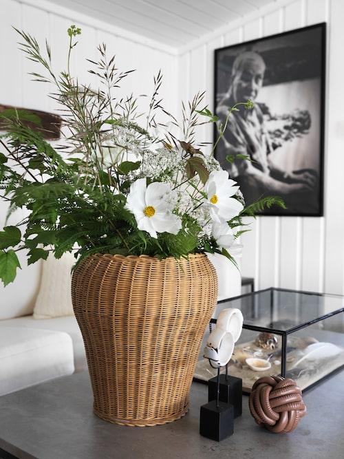 Somrigt stileben med blomster i en gammal garnkorg och strandfynd. Svartvitt foto som föreställer pappa Ragnar, taget av Toves dotter Nina.