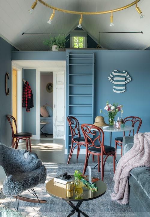 I den ena änden av gästhuset ryms ett sovloft ovanpå sov- och badrum. Den randiga sjömanströjan – i trä – hittade Catherine på en utställning på Konstnärshuset i Stockholm. Matbord Officina med marmorskiva, av Ronan & Erwan Bouroullec för Magis, och en mix av omlackade Thonetstolar.