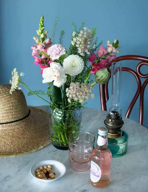 Blomsterfånget är plockat i trädgården. Fotogenlampa Skeppsholmen i klarglas, Fentimans botaniskt brygda Rose Lemonade dricks i små nätta glas.