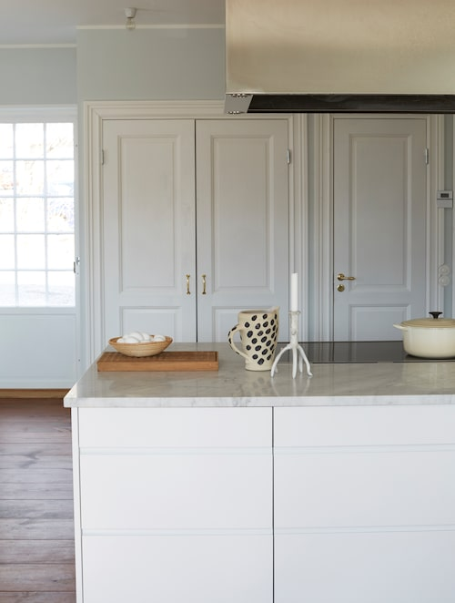 Köket är byggt av Ikea-stommar med luckor från Picky living. Bakom dörrarna i bakgrunden döljer sig kyl och frys samt skafferi. Både fläkten och diskhon är specialtillverkade av Litsby industrier. Karaff från Lena Scharp keramik.