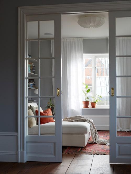 I anslutning till vardagsrummet ligger tv-rummet, inrett med vita schäslonger från Ikea, kuddar från Mimou och taklampa från Watt & Veke.