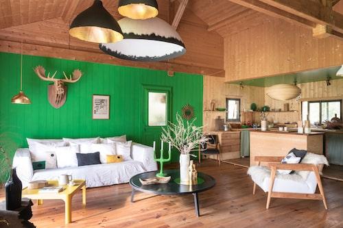 Vardagsrummet har en härlig volym med tak öppet till nock. Målade tak och väggar i starkt grönt livar upp och moderniserar den rustikt träpanelade interiören.