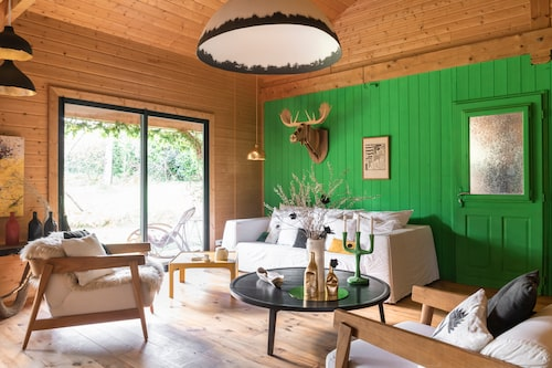 Möblerna kontrasterar och uppdaterar husets rustika stil. Soffa, fåtöljer och runt bord från Gervasoni. Det gula bordet är vintage, vaserna är hemgjorda. Ljusstake från Muuto, älgtrofé i kartong från Big game, kuddar från Jacques design och Niaréla rue 420. Lamporna är parets egna, från Rom&An.