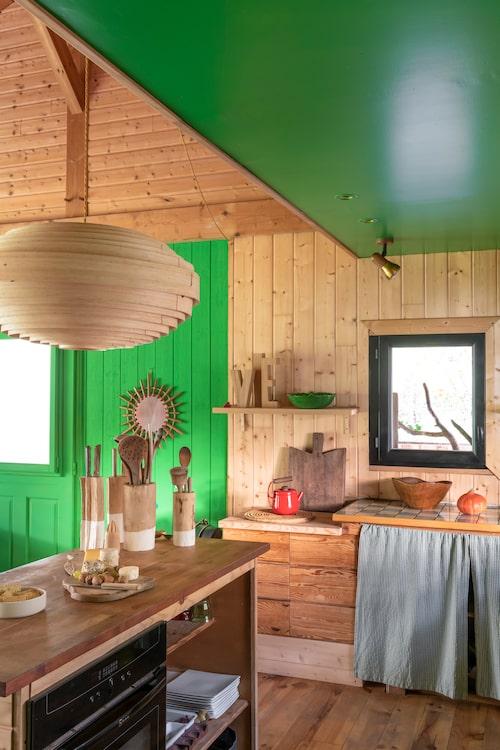 Paret har själva byggt köksinredningen – som illustrerar att det går utmärkt att blanda olika träslag. Ju fler desto bättre! Taklampan är från holländska Ay illuminate, spotlighten är ett vintagefynd.