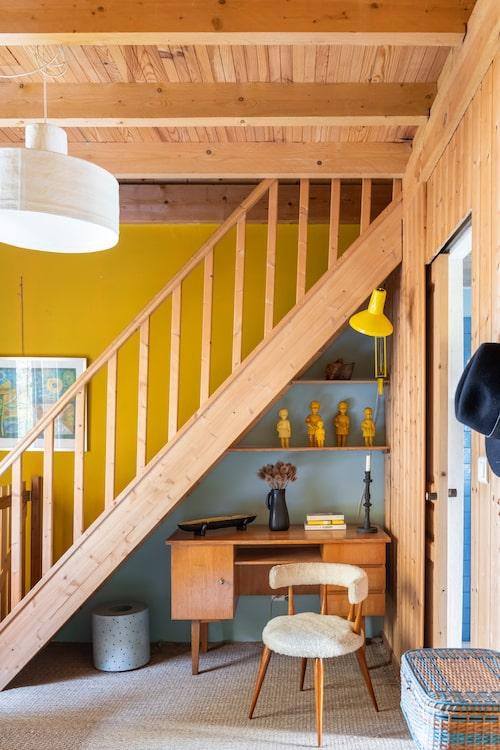 Under trappan finns en liten arbetshörna med 50-talsmöbler. Väggar och föremål i saffransgult, blekturkost och svart får furuinredningen att kännas uppdaterad och modern.