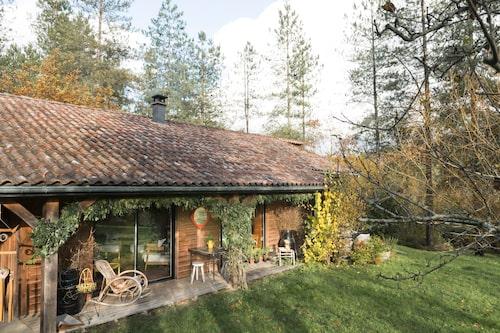 Trähuset uppfördes för tio år sedan och är omgivet av en hektar orörd skog. Verandan är möblerad med secondhandmöbler.