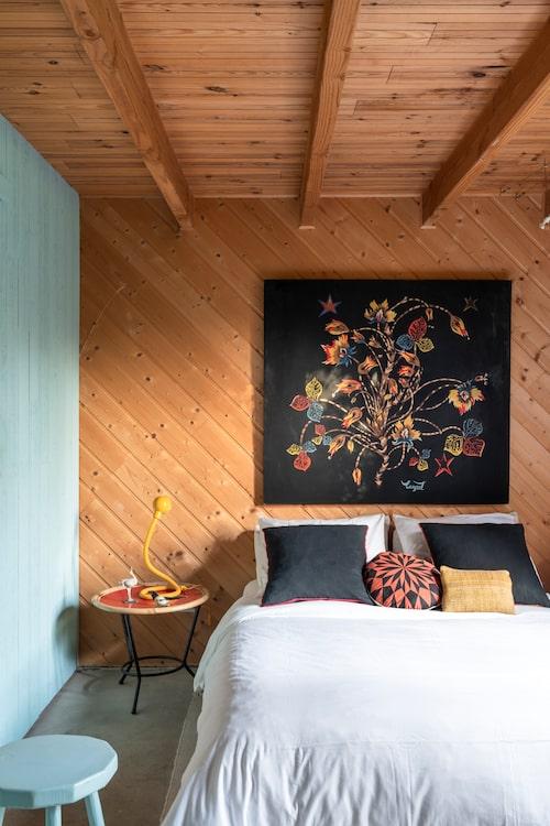 Panel på längden eller tvären? Anne och Romain satte den på sniskan! Den härliga väggtextilen av Jean Lurçat agerar visuell sänggavel och anger färgtonerna för rummets övriga inredning, bland annat den ljusblå fondväggen till vänster. Kuddar från Gervasoni och Ferm living,