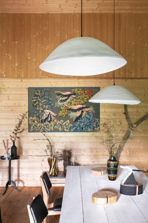Över matplatsen hänger parets egna lampskapelser, från Rom&An. Det rustika bordet är ett hemmabygge. Väggtextilen med flamingor är från 50-talet, av franska konstnären och textildesignern Robert Debieve. Dess färgpalett tas upp i vasen på bordet.