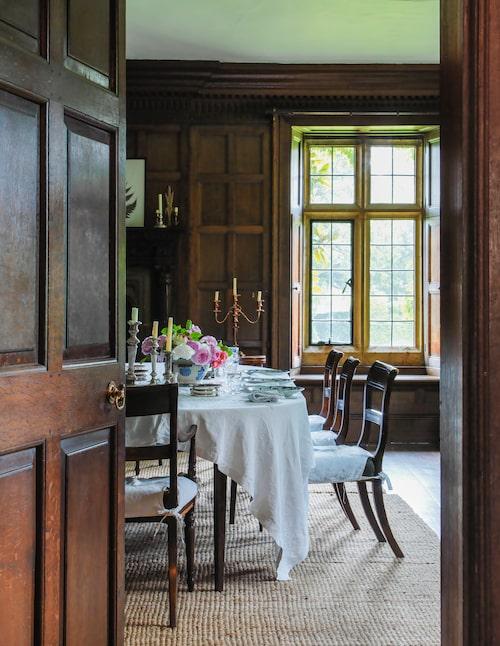 Genom tunga ekdörrar träder man in i matsalen, även den klädd i ekpanel. Utanför de blyinfattade fönstren breder trädgårdens härlighet ut sig.