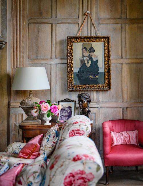 En målning upphängd i tygband, signerad Herbert James Gunn (1893–1964) pryder väggen i biblioteket. De vackra ekpanelerna återkommer på flera håll i huset. Och överallt blommor från trädgården, här i samspråk med de chintzklädda fåtöljerna.