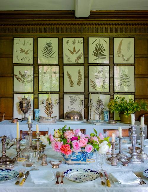 Dukat för bjudning i matsalen! Trädgårdsrosorna har arrangerats i en soppterrin och mängder av silverljusstakar i olika höjder skänker glans åt bordet. På väggen inramade pressade ormbunksblad.