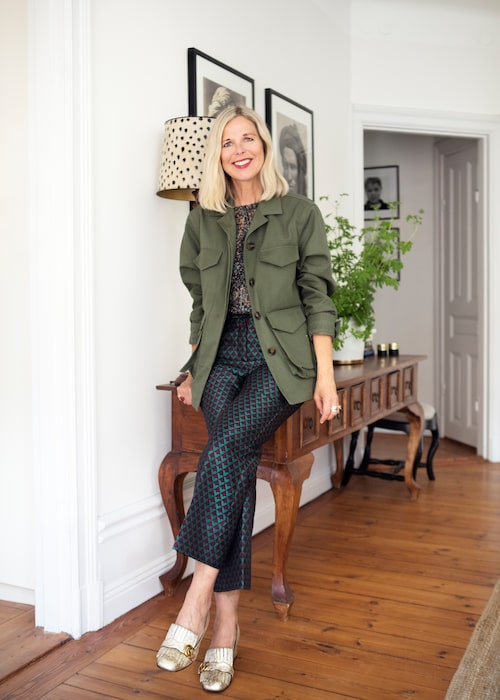 Catarina Midby i sitt hem klädd i jacka från Totême, byxor och blus från H&M och skor från Gucci.