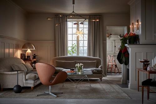 Mjuka gråbeige toner skapar en ombonad känsla i vardagsrummet. Soffor från Jio och soffbord, Eilersen. Taklampa 101 Copenhagen, och i hörnet Magistrettis bordslampa Atollo för Oluce. Mattan är köpt i Spanien.