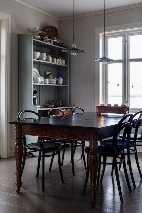 """Det stora matbordet är ett lyckosamt köp på Blocket, stolarna är från Länna möbler och """"några av få möbler som är helt nya i vårt hus"""". Den gamla hyllan är fylld med sköna samlingar."""