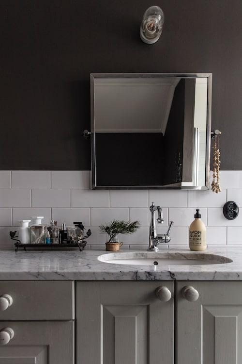 Badrummet har en tidlös känsla med vitt kakel, marmorskiva och en gråmålad kommod som Anna och Fredrik byggt själva av köksstommar. Knopparna kommer från Byggfabriken.se, blandaren kommer från sekelskifte.se. Spegeln är en utgången modell från Ikea.