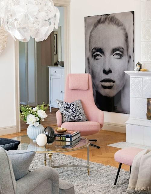 I vardagsrummet finns den pampiga kakelugnen bevarad. Taklampan heter Hope och kommer från Luceplan. Den rosa snurrfåtöljen från Vitra är en av Karins favoritmöbler. Fotokonst Gazing still av Igor Vasiliadis.