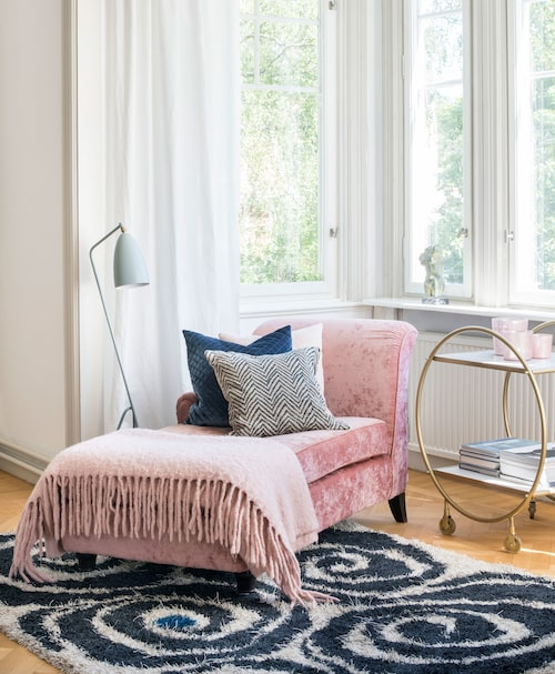 Plats för avkoppling. Den rosa divanen i vardagsrummets burspråk kommer från Englesson. Drinkvagnen är från Newport och mattan Virvel kommer från Kasthall.