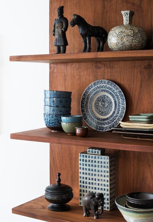Bokhyllan i valnöt har Martina designat. Här har keramik, träsnideri och reseminnen från Indien och Kina sina självklara platser.