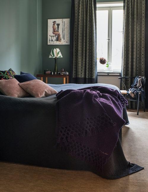 Sovrummet är inrett med mörka färger som harmonierar väl tillsammans. På sängen, en violett alpackapläd och rosa sammetskuddar, Anna Charlotte atelier. Gardinerna är sydda av sarier i siden, från Indien. Lampfot i mörkgrönt glas från Bergboms, köpt på Auctionet, med skärm i tyget Stensöta från Svensk tenn.