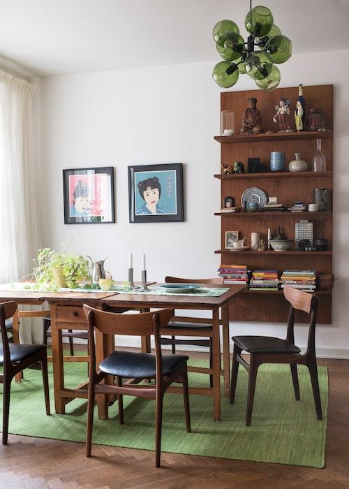 I matsalen hänger två litografier av Maria Manuela Vintilescu. Bokhyllan är i Martinas egen design, tillverkad i valnöt på Pondus snickeri. Matbordet är arvegods från Martinas farfars systrar, teakstolarna är dansk 60-talsdesign, köpta på Lauritz. Taklampan Tage, Care of Bankeryd. Den gröna kelimmattan under matbordet kommer från Rug vista.