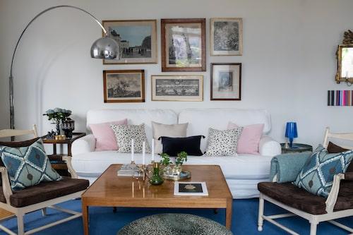 Mattan i vardagsrummet har hängt med i 18 år och kommer från Linoleumkompaniet. Golvlampan är en variant av Arcolampan och Susanne har haft den sedan 80-talet. Soffan köptes på Ikea för 15 år sedan och de prickiga kuddarna är från Familjen Fogelmarck. Tavlorna är arvegods.