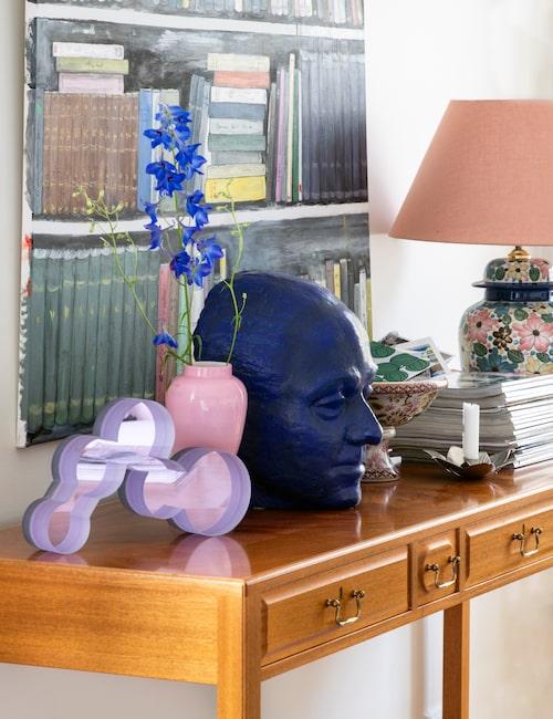 I vardagsrummet står det här sidobordet från Svenskt tenn. Den rosa vasen är arvegods, skulpturen bredvid är gjord av Inger Andersson, verksam vid Gustavsberg. Det blå huvudet föreställer Susannes farfar Kurt, men skulptören är okänd. Tavlan är målad av Susanne Langenskiöld.