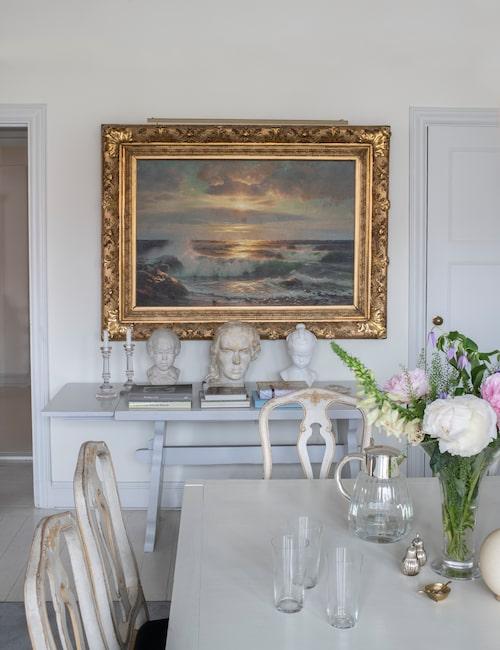 Allmogebordet som används som sidobord hittade Susanne och Jesper i källaren där de bodde tidigare. Tavlan är arvegods. Bysten Flickan med flätor är en kopia av en 1700-talsbyst. Huvudet i mitten föreställer Susannes farmor och är gjord av finländaren Gunnar Elfgren. Glasljusstakar från Oscar & Clothilde.