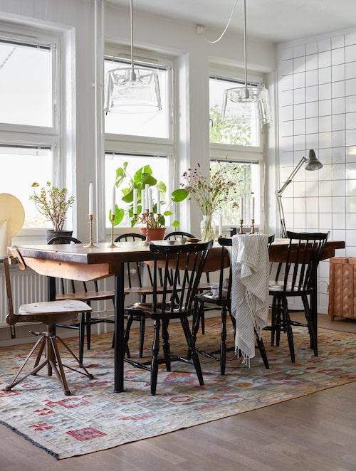 Bordet är ett gammalt mangelbord som Johanna har satt ben på. Stolar från loppisar och Blocket som målats om. Matta, Bargi. Skrivbordslampa, loppisfynd.
