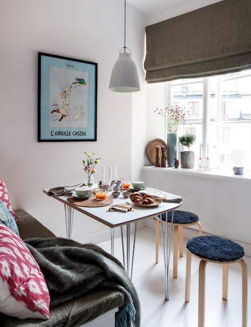 Compact living 2.0. I köket står en avkapad halva av ett Superellipsbord, den andra, nyttjas i huset på landet. Taklampa Caravaggio, Fritz Hansen och pallar från Ikea. Tekanna av Sebastian Hägelstam, bordsborste, Iris hantverk.