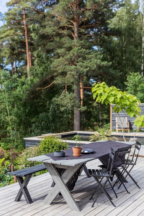 Sittplats med utsikt. I bakgrunden skymtar poolen, som har fått en svart poolduk för att smälta ihop med skogen.