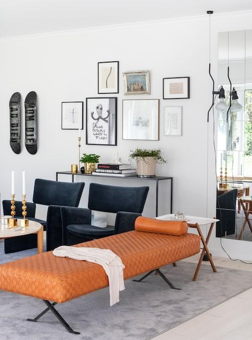 """Den cognacsfärgade dagbädden i design av Enzo Mari lyser upp vardagsrummet. Färgen går igen i soffbordets ben i mahognyträ. Sammetsklädda karmstolar från Massproductions, sidobordet i metall och glas från Familjen Fogelmarck – att blanda material är Alines sätt att skapa rumslighet. Spegelvägg från Ikea, Aline har klistrat upp de självhäftande rutorna med """"känslan av tonårsrum från 80-talet"""". På tavelväggen en barnteckning, en liten oljemålning av konstnärinnan Esther Gehlin, och maken Henriks skateboardar. """"Han är gammal skejtare, så de måste ju få vara med""""."""