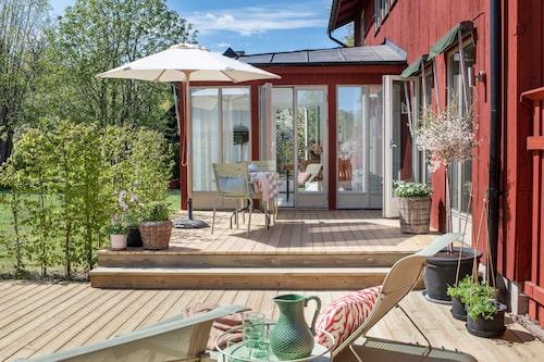 Husets vardagsrum är byggt i T-form med en matsal som sticket ut på verandan. Ljuset silas genom gardiner från Astrid. Verandastolarna är från Fermob och bordet från Ikea. Den rutiga duken har Aline sytt av en gammal stuvbit.