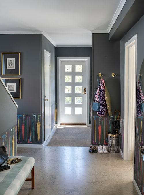 """Hallen är husets enda mörka rum, de grå väggarna står i kontrast till de ljusa rummen i resten av huset. Paraplytapeten från Fornasetti är ett bra exempel på Alines humor. """"Inredningen måste kunna vara lättsam"""", säger hon."""