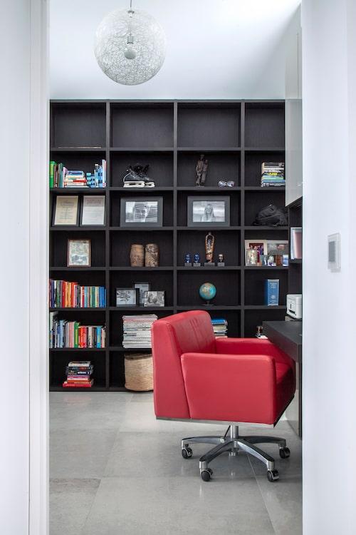 I husets privatare delar, som biblioteket arbetsrummet, råder en friare, varmare stämning med illröd skrivbordsstol och mörk bokhyllevägg från Lema.