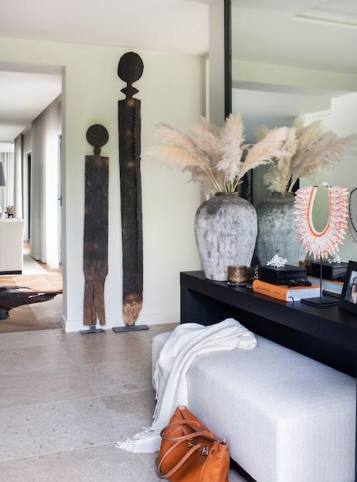 """I entrén möts man direkt av kalkstensgolvet som finns i stora delar av huset. """"Träfigurerna vid väggen ska symbolisera mig och Harald"""", säger Caroline Behrn med glimten i ögat. Trädekorationerna, den svarta bänken och den vita sittbänken kommer från Slettvoll."""