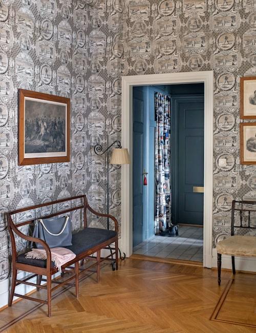 """Motivet på tapeten Les vues de Paris, Parismonument i grådis, skapades i början på 1800-talet och har tagits fram på nytt av Marvic textiles. """"Vi har haft den förut, älskar man kopparstick är det här tapeten!"""" Soffan i senempire, danskt 1800-tal, hittade de hos Kisek i Båstad. Kopparstick av Napoleon med generaler."""