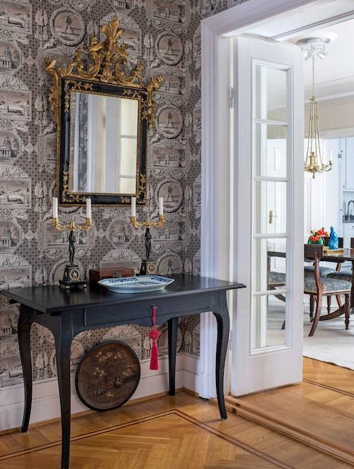 Skrivbordet Österbybruk ingick i Ikeas 1700-talsserie. Empireljusstakarna i brons är baltiska, stekfatet och huanghuali-asken är kinesiska och spegeln är ett italienskt barockfynd. Brickan med reliefdekor är japansk från meijiperioden.