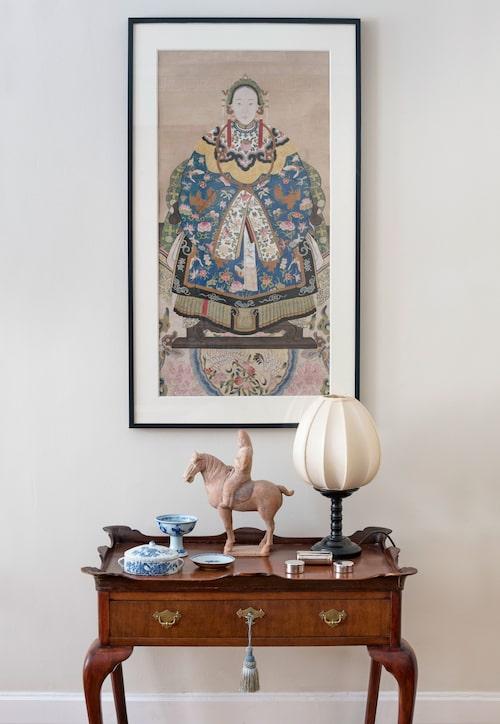 """Bordet är i Queen Anne-stil från 1800-talet. """"Vi har två likadana vi köpt med tjugo års mellanrum på Auktionsverket, och när vi provade nyckeln visade de sig vara ett par! Den söta hovdamen på väggen är från 1800-talets mitt, och hästen i lergods från Tangdynastin (618–906 eKr). Skulpturen låg sönderslagen i bitar hos en kund som hotade slänga bort den, så jag räddade den och konservatorn Bouke de Vries pusslade ihop den så skickligt att det inte syns."""""""