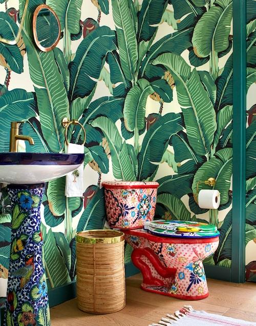 Ingen tråkig toalett. Handfat och toalett i mönstrad mexikansk keramik. Tapeten Martinique banana leaf i nytillverkning av Donghia.