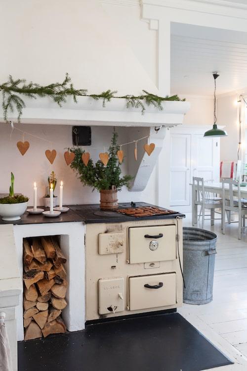 Den gamla vedspisen i gjutjärn sprider en härlig värme i köket. Växter är viktiga stämningsskapare på julen. Mari har köpt lummer och lagt på spiselkransen och planterat amaryllis i en vit soppskål. Soptunnan är ett kärt minne från Australien, där den stod ute på trottoaren för tömning.