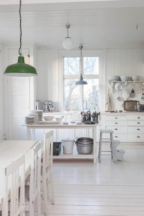 Köksskåpen i original från 20-talet, men två extra lådor har tillverkats och allt har vitmålats. Bänkskivan är utbytt och man har satt in en ny porslinsho. Blandaren har Mari beställt från England, och köksön lät hon en hantverkare snickra ihop. Den vita emaljhinken används som kompostbehållare. Industrilamporna och hyllan är köpta på olika loppisar. Matbordet är från Australien och tillverkat av återvunnet trä.