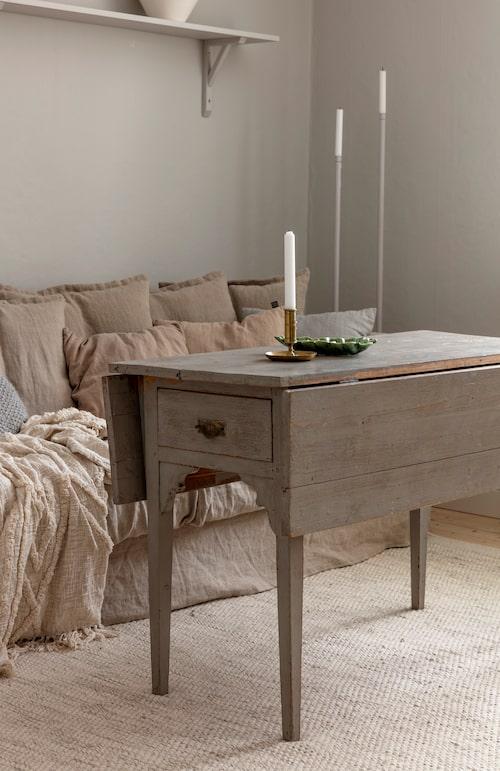 Ett loppisfyndat slagbord har blivit soffbord i allrummet. Naturmaterial som linne, ull och fårskinn ger värme till inredningen.