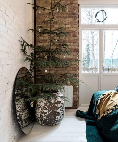 En av tegelväggarna i Simons sovrum har fått vara rå medan de andra har målats i vitt. Även här får en stor urna agera julgransfot. Spegel från Iems.