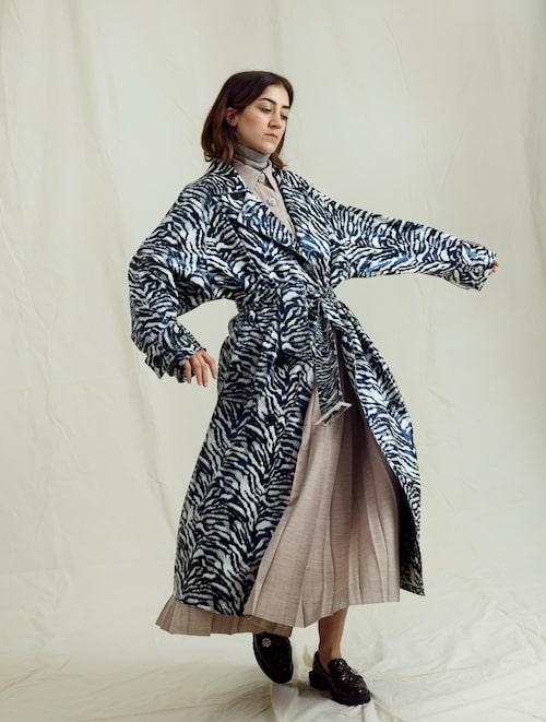 Gizem Kling Erdogan i kappa från Stand Studio, och klänning, Ganni. Polotröja, Stenströms. Loafers, Ganni.